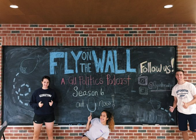 Fly on the Wall staff stand in front of a chalk board in Bulldog Alley