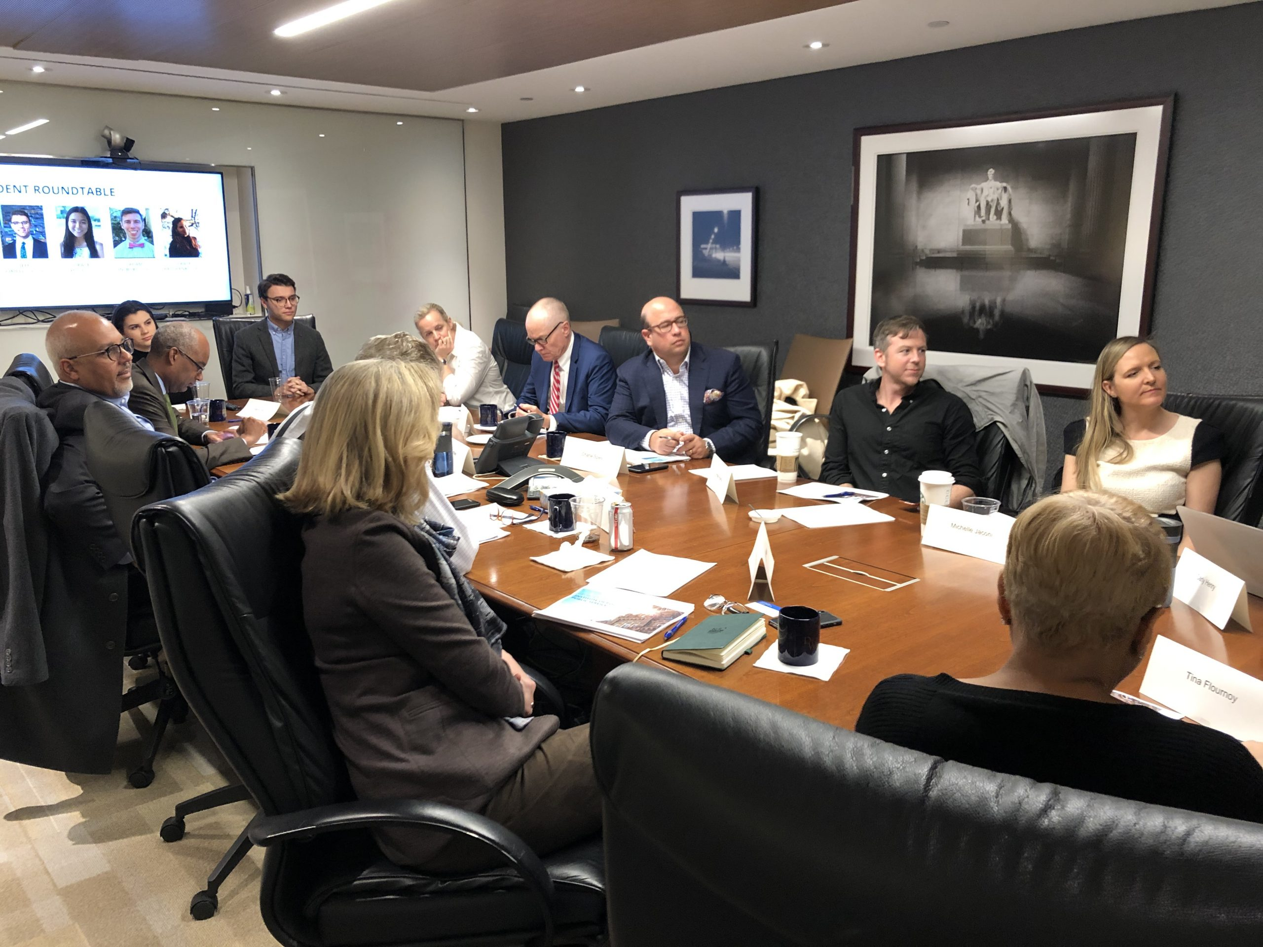 Event participants around a large conference table watching Zoom screen